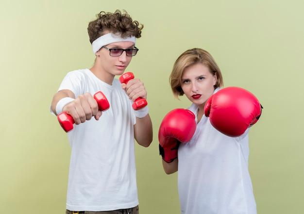Jonge sportieve paar man met halters naast zijn vriendin met bokshandschoenen poseren over licht