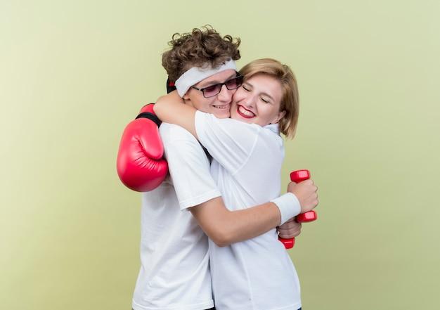 Jonge sportieve paar vrouw met bokshandschoenen knuffelen haar vriendje met bokshandschoenen blij en positief staande over lichte muur