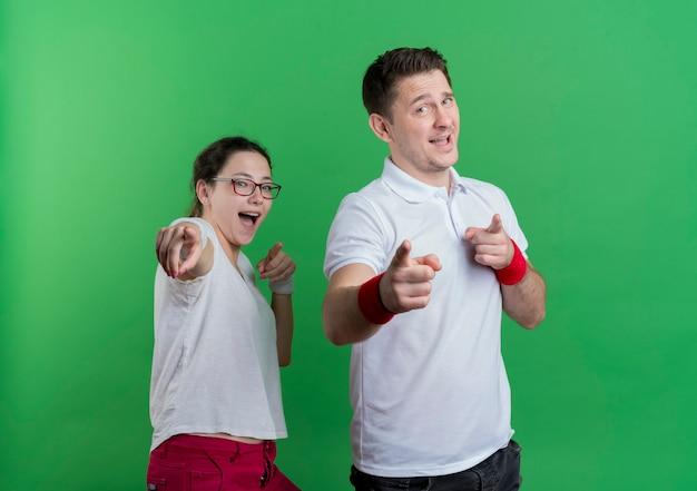 Jonge sportieve paarman en vrouw die met gelukkige en opgewekte vingers richten die zich over groene muur bevinden