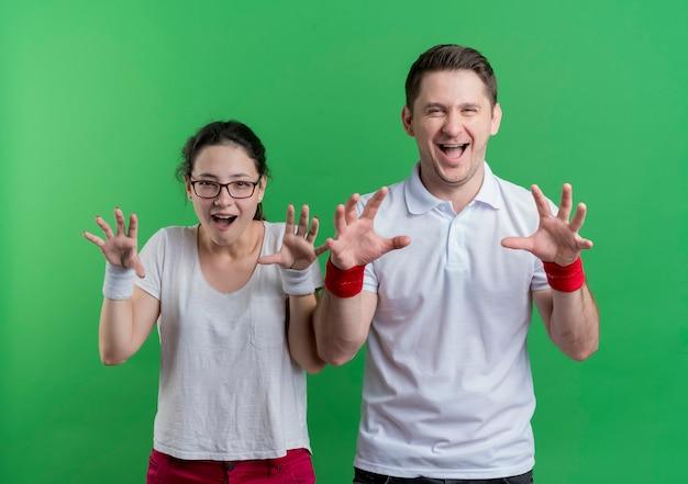 Jonge sportieve paarman en vrouw die met handen bedreigen die pret hebben die zich over groene muur bevinden