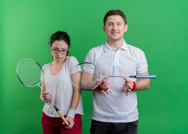 Jonge sportieve paarman en vrouwenholding rackets voor tennis glimlachend status over groene muur