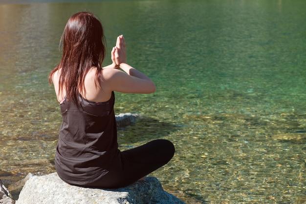 Jonge sportieve vrouw beoefenen van yoga in zwarte sportkleding in de buurt van de rivier of het meer met transparant water