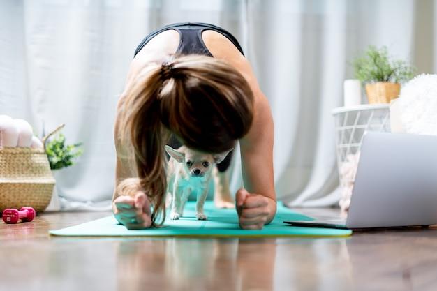 Jonge sportieve vrouw die aan het trainen is en laptop thuis gebruikt in de woonkamer die yoga of pilates doet