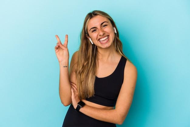 Jonge sportieve vrouw die aan muziek met geïsoleerde oortelefoons luistert vreugdevol en zorgeloos toont een vredessymbool met vingers.
