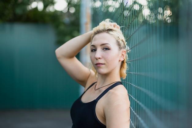 Jonge sportieve vrouw die camera bekijkt