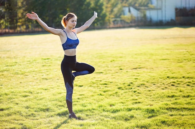Jonge sportieve vrouw die de oefeningen van de yogageschiktheid op warme de zomerdag in openlucht doen.