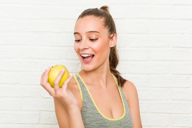 Jonge sportieve vrouw die een appel houdt