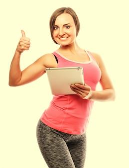 Jonge sportieve vrouw die een digitale tablet gebruikt