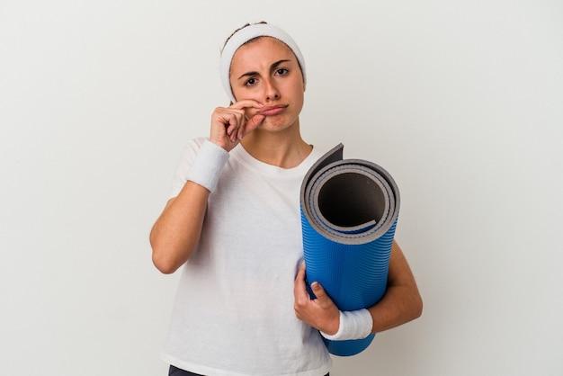 Jonge sportieve vrouw die een mat met vingers op lippen houdt die een geheim houden.