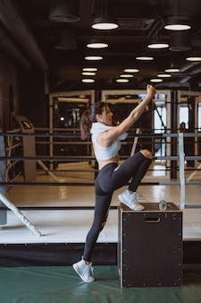 Jonge sportieve vrouw die een selfie met mobiele telefoon nemen bij gymnastiek.