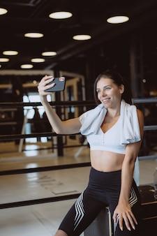 Jonge sportieve vrouw die een selfie met mobiele telefoon op sportschool