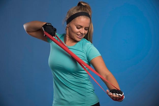 Jonge sportieve vrouw die haar armspieren uitrekt.