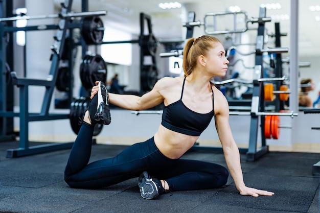 Jonge sportieve vrouw die haar been in gymnastiek uitrekt.