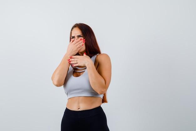Jonge sportieve vrouw die haar hand op de neus houdt