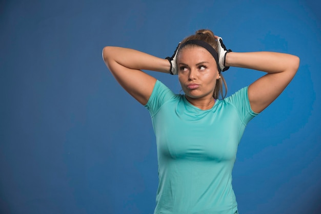 Jonge sportieve vrouw die haar hoofd met twee handen houdt.