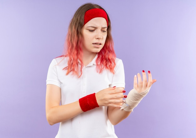 Jonge sportieve vrouw die haar verbonden pols raakt die pijn voelt die zich over purpere muur bevindt
