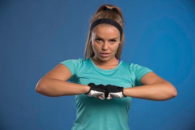 Jonge sportieve vrouw die haar vuisten verenigt.