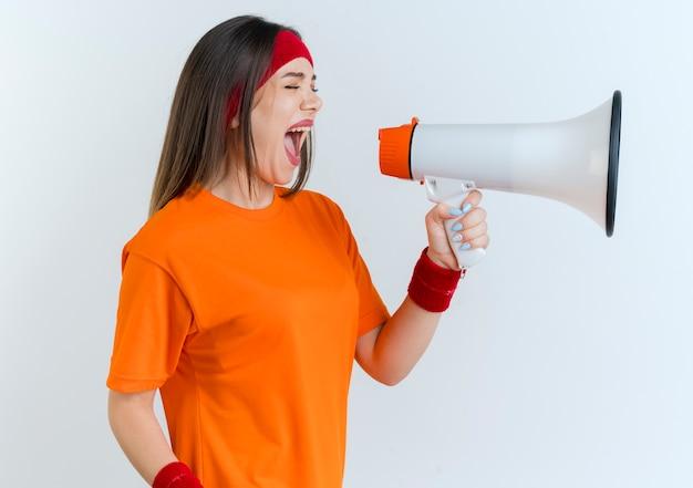 Jonge sportieve vrouw die hoofdband en polsbandjes draagt die zich in profielmening bevinden die in luide spreker met gesloten ogen schreeuwen
