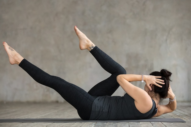 Jonge sportieve vrouw die kruiselingse oefening doet