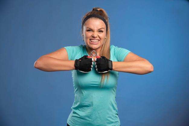 Jonge sportieve vrouw die met een hand het uitrekken zich gom probeert op te lossen.