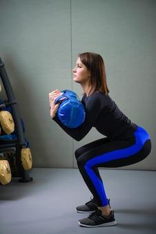 Jonge sportieve vrouw die met geschiktheidstas bij gymnastiek uitwerken