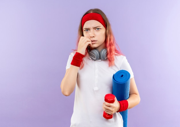 Jonge sportieve vrouw die met hoofdtelefoons yogamat houdt die verward en bezorgd kijkt die zich over purpere muur bevindt