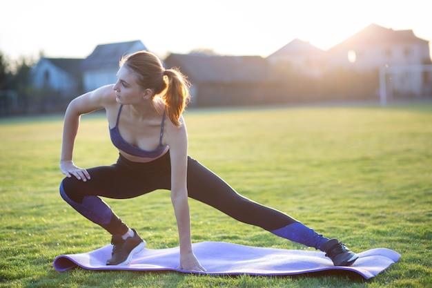 Jonge sportieve vrouw die oefening doet alvorens in openlucht op ochtendgebied in openlucht uit te voeren.