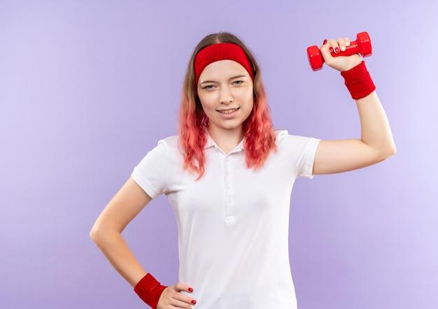 Jonge sportieve vrouw die oefeningen met één halter doet die zich zelfverzekerd over purpere muur glimlachen