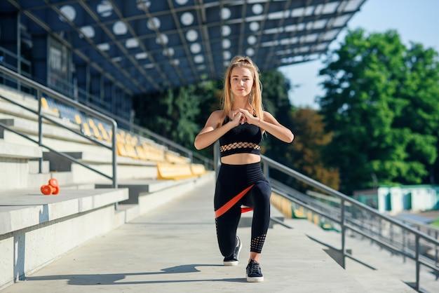Jonge sportieve vrouw die oefeningen met elastiekje doen openlucht