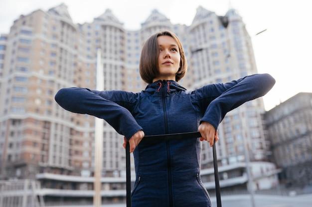 Jonge sportieve vrouw die oefeningen met elastiekje openlucht doet