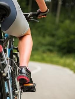 Jonge sportieve vrouw die op bergfiets berijdt.