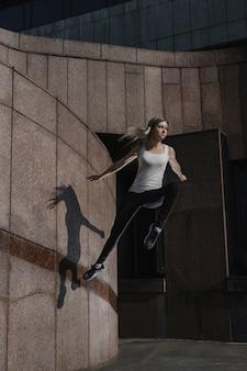Jonge sportieve vrouw die parkour in stad doet