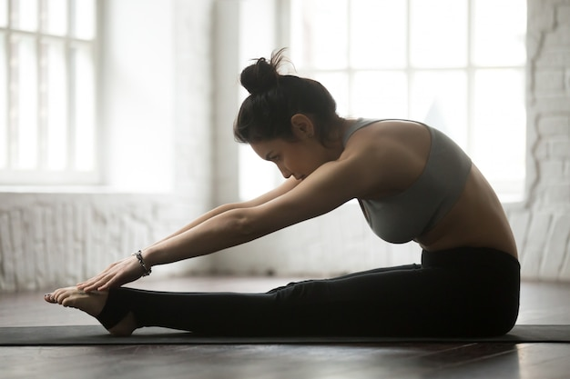 Jonge sportieve vrouw die pilates spine stretch forward-oefening uitoefenen