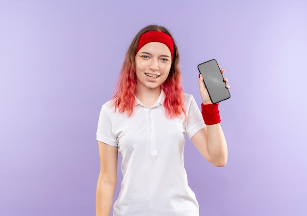 Jonge sportieve vrouw die smartphone toont die met blij gezicht glimlacht dat zich over purpere muur bevindt