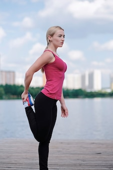 Jonge sportieve vrouw die sporten in openlucht, fitness oefeningen doet.