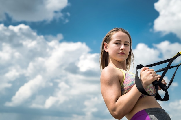 Jonge sportieve vrouw die trx-oefeningen, blauwe hemel met wolk op oppervlakte, in park doet
