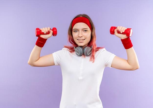 Jonge sportieve vrouw die twee domoren houdt die oefeningen met glimlach op gezicht doen die zich over purpere muur bevinden