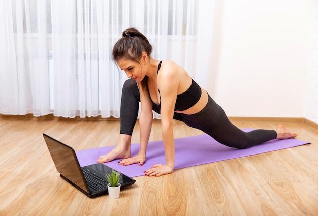Jonge sportieve vrouw die yoga beoefent op een paarse mat en naar haar laptop kijkt
