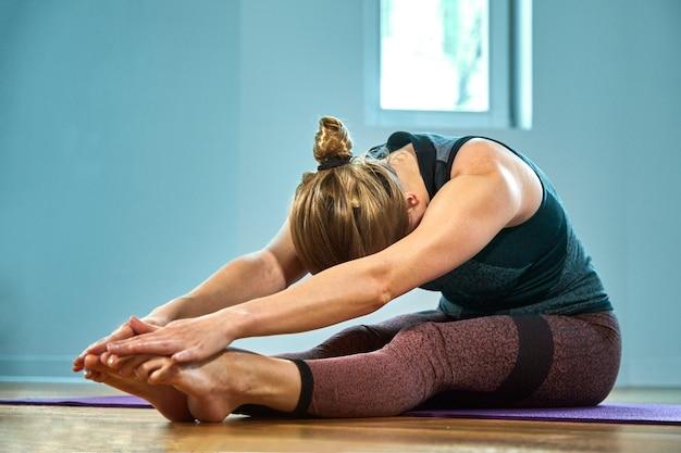 Jonge sportieve vrouw die yoga beoefent, uitwerkt, sportkleding, broek en top draagt, binnen close-up, yogastudio