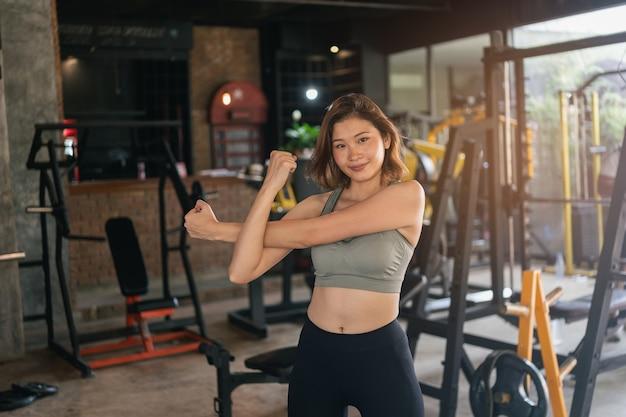 Jonge sportieve vrouw die zich uitstrekt bij sportschool, fitness sport concept