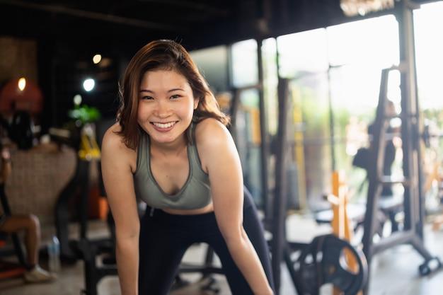 Jonge sportieve vrouw die zich uitstrekt op sportschool, fitness sport concept