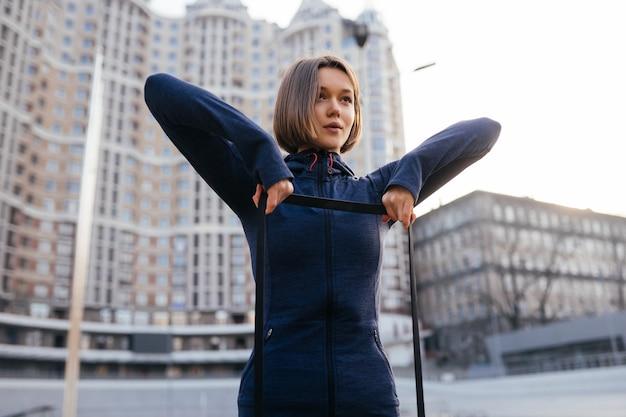 Jonge sportieve vrouw doet oefeningen met rubberen band buiten doing
