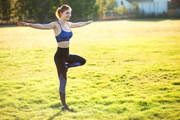 Jonge sportieve vrouw doet yoga fitness oefeningen op warme zomerdag buitenshuis.