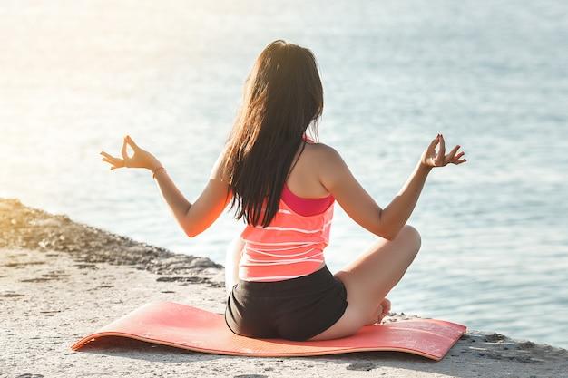 Jonge sportieve vrouw doet yoga oefeningen op het strand