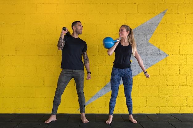 Jonge sportieve vrouw en man die in de gymnastiek uitwerken