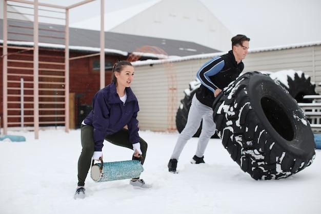 Jonge sportieve vrouw en man training met zware band, buitenshuis