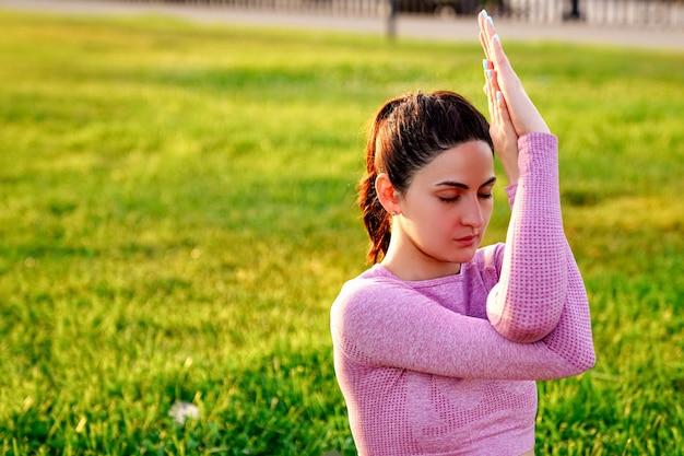 Jonge sportieve vrouw het beoefenen van yoga in een roze yogakostuum bij zonsopgang in het park