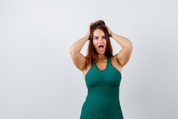 Jonge sportieve vrouw in een groene bodycon