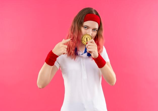 Jonge sportieve vrouw in hoofdband die gouden medaille toont die met vinger ernaar richt die zich zelfverzekerd over roze muur bevindt