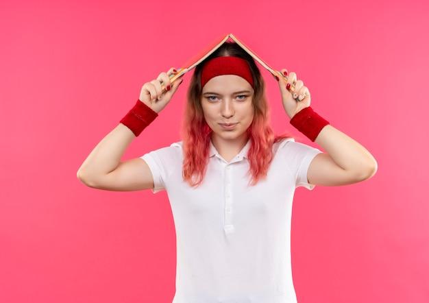 Jonge sportieve vrouw in hoofdband die haar hoofd bedekt met twee rackets voor tafeltennis glimlachend staande over roze muur
